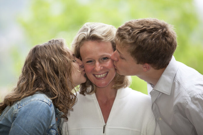 mother son daughter: son and daughter kissing mother on cheek