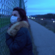 divorce during covid-19: woman standing at fence with surgical mask on