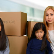 move away with the child after divorce: mother and daughters surrounded by moving boxes