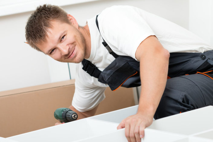 rent a husband: handsome man smiling doing handy work