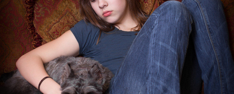 your teen cope with divorce: sad teen girl on couch with dog