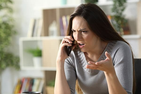 Woman talking to angry ex on the phone who needs to establish boundaries in their co-parenting communication