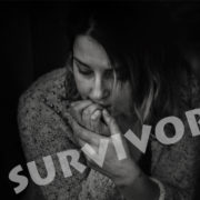 DOMESTIC VIOLENCE SURVIVOR: Woman in dark room, word survivor written across her image