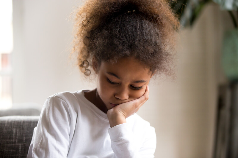 truth about children and divorce: sad african american girl with face in hand